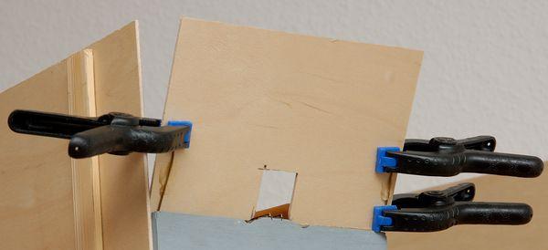 Die Seiten werden mit UHU Kraft an 1 mm-Messingdrähte geklebt. Sie stecken in schrägen Bohrlöchern und werden später hoch gebogen.