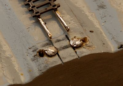 Die Schrauben und die Rückseiten der Schienenprofile sind verzinnt. Die Löcher für die Kabeldurchführungen sind nur 2,5 mm im Durchmesser, wirken aber wie Krater.