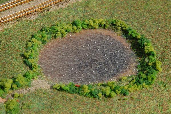 Der unmotiviert in der Landschaft liegende Teich aus Wasserfolie ist völlig zugestaubt. Die umliegenden Pflanzen entsprechen nicht mehr dem Stand des Landschaftsbaus.