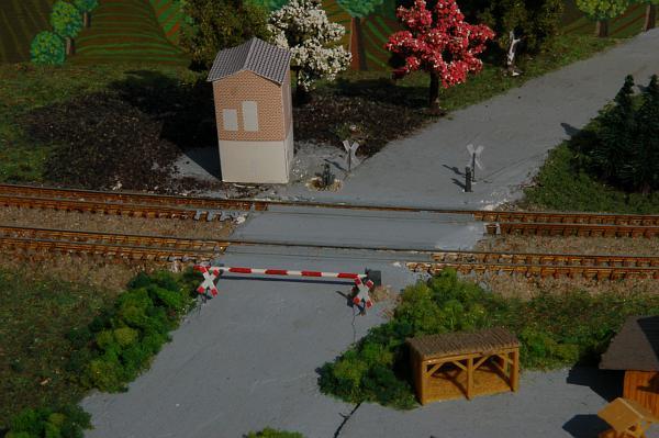 Am Bahnübergang ist ein Schrankenbaum in irgendeiner Messehalle geblieben. Der Posten aus Papier, ist für einen einsamen Schrankenwärter völlig überdimensioniert. Der Übergang ist zu breit.