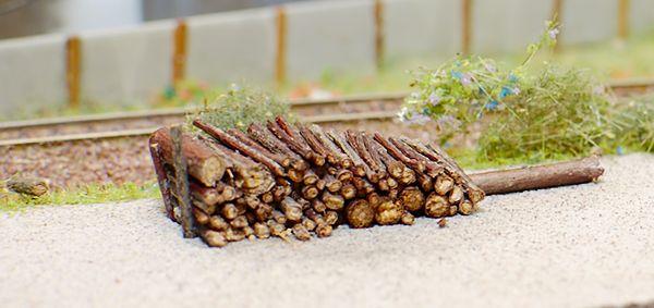 Der Holzstapel wird rechts von einem dickeren Stamm gegen Abrollen gesichert.
