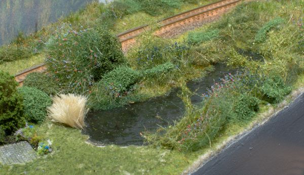 Das Ufer ist mit viel Gebüsch bewachsen.