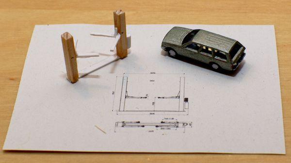 Die Hebebühne und das kaputte Auto auf der Konstruktionszeichnung