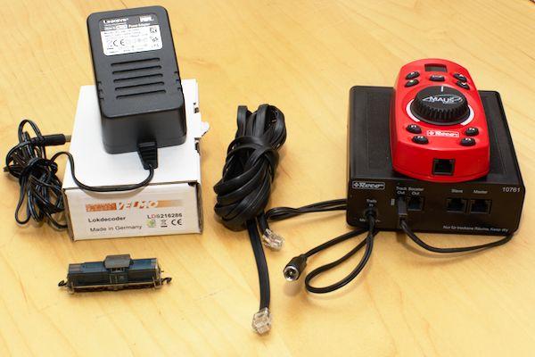 Kleine Lok, große Komponenten: Der Decoder wird in einer großen Schachtel geliefert. Darauf liegt das vorhandene Netzteil, in der Mitte ist das sechspolig belegte Kabel und rechts die Roco-Digitalkomponenten.