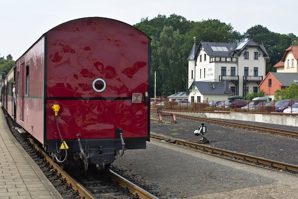 """Der Zug steht abfahrbereit am Bahnhof. Rechts liegt das sehr empfehlenswerte Hotel """"Villa Sommer""""."""