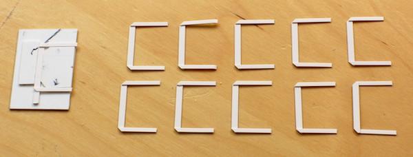 Die Serienproduktion der Bleche. Links liegt die Lehre. Am schwarzen Strich werden die Ecken diagonal abgeschnitten.