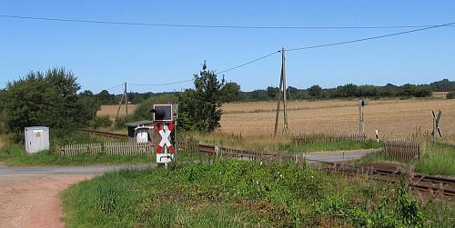 Auch in heutiger Zeit gibt es noch solche eingezäunte Bahnübergänge. Dieser hier ist in Mielsdorf an der Strecke Bad Oldesloe-Bad Segeberg. Während der Zaun hinten links noch als Schutz für das Holzhaus dienen könnte, enden die Zäune rechts am Andreaskreuz.